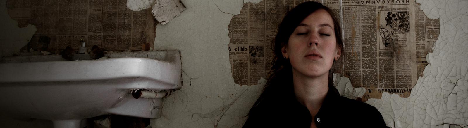 Eine Frau sitzt mit geschlossenen Augen an eine Wand ohne Tapeten gelehnt.
