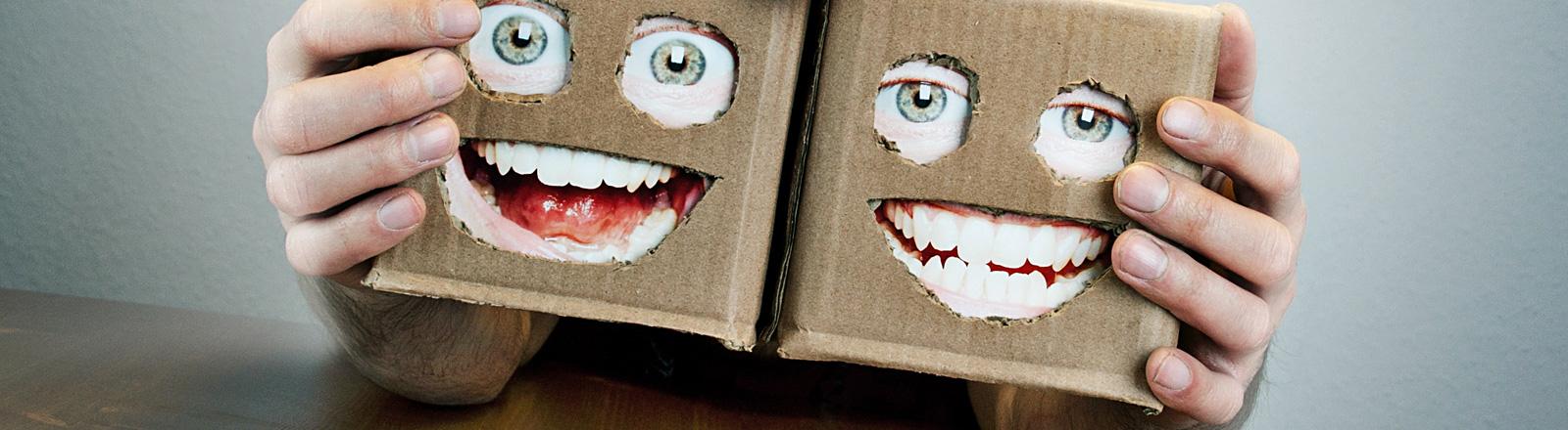 Zwei Hände halten zwei Kisten mit jeweils drei Löchern. Hinter den Löchern sind Fotos von Augen und Mündern geklebt. Dadurch wirken die Kisten wie Gesichter.