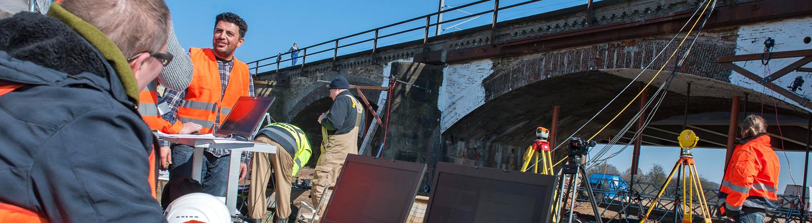 Wissenschaftler stehen (17.03.2016) vor der historischen Eisenbahnbrücke über die Aller in Niedersachsen. Sie machen einen Belastungstest der Brücke; Foto: dpa