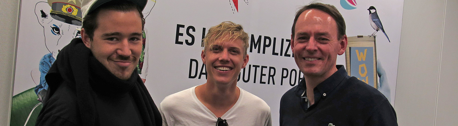 James Hunt, Tyrone Lindqvist von der Band RÜFÜS stehen neben DRadio Wissen-Moderator Manuel Unger.