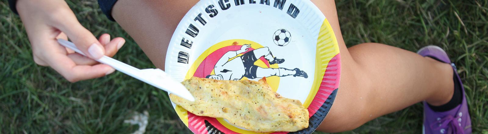 Auf den Oberschenkeln einer Frau liegt ein Papierteller auf dem ein Fußballer abgebildet ist. Darüber steht Deutschland.