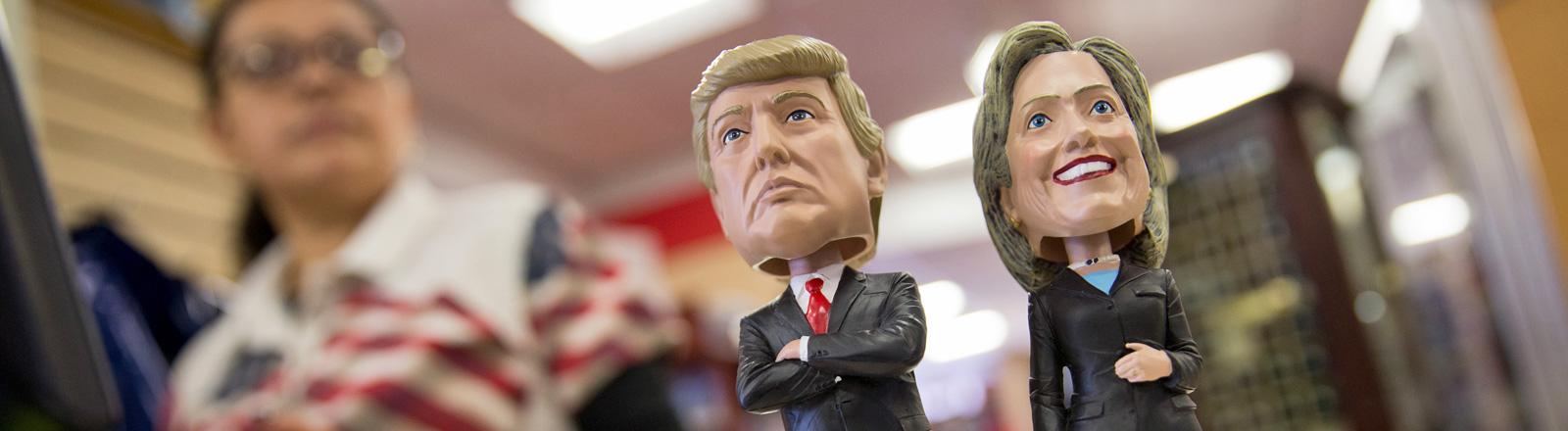 Wackelfiguren mit stilisierten Köpfen des republikanischen Kandidaten Donald Trump und der demokratischen Kandidatin Hillary Clinton stehen in einem Laden zum Verkauf; Foto: dpa
