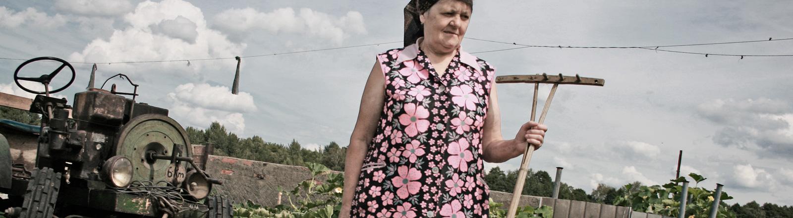 Eine ältere Frau steht im Garten und hält einen Holzrechen in der Hand. Links neben ihr parkt ein alter Traktor.