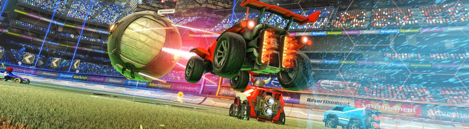Eine Spielszene aus Rocket League: In einem Fußballstadion rasen drei Autos auf einen übergroßen Ball zu.
