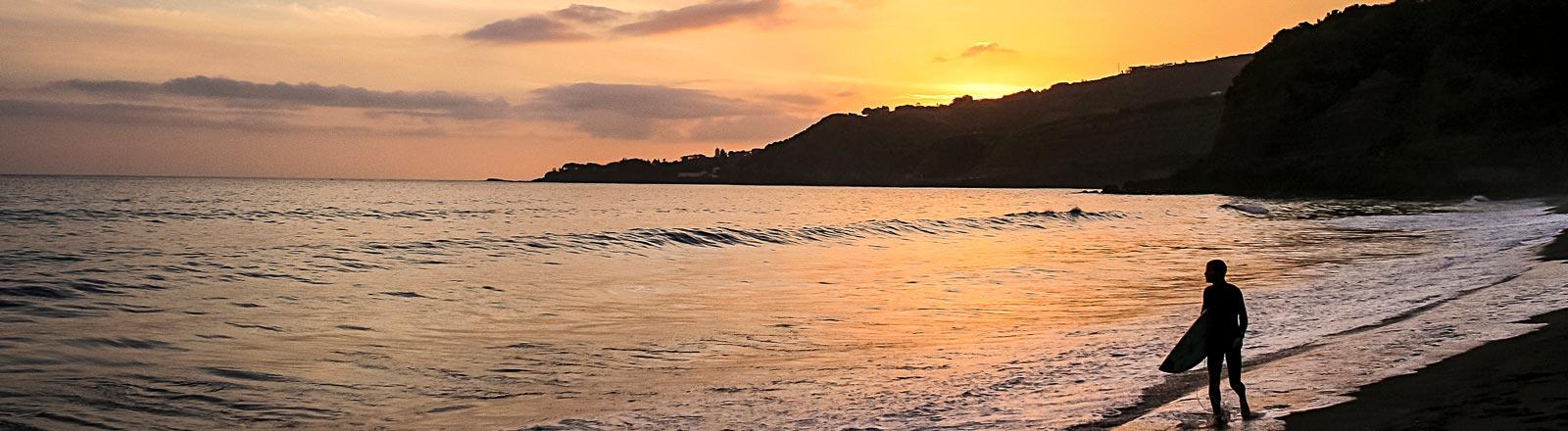 Ein Surfer an einem Strand einer Azoren-Insel.