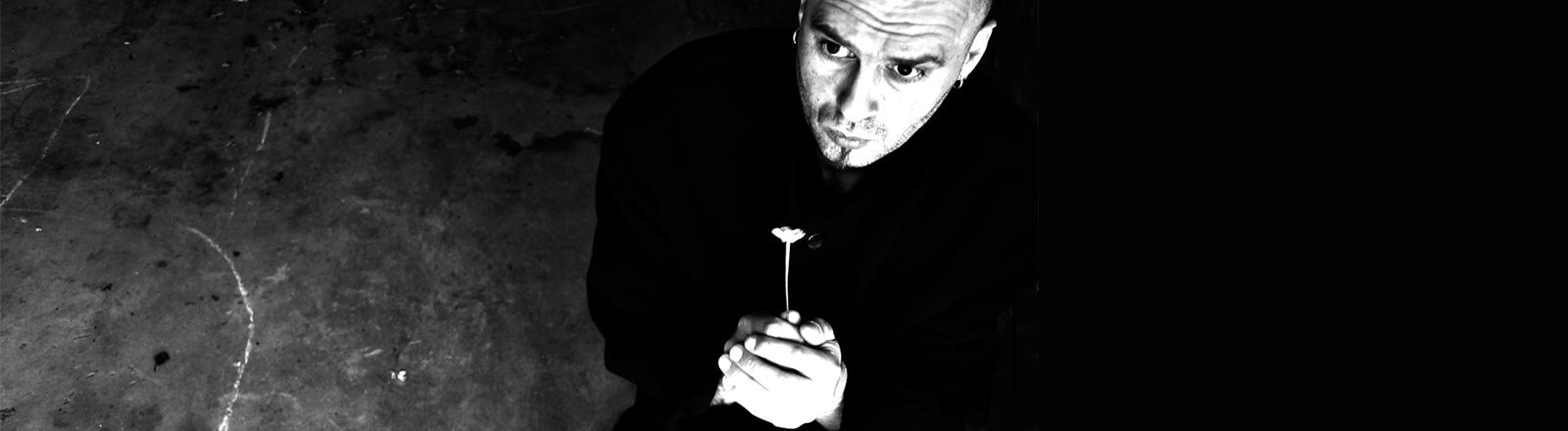Ein Mann hält traurig eine Blume in der Hand.