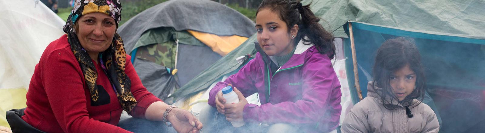Eine irakische Mutter und ihre beiden Töchter sitzen an einer Feuerstelle im Camp von Idomeni und kochen.