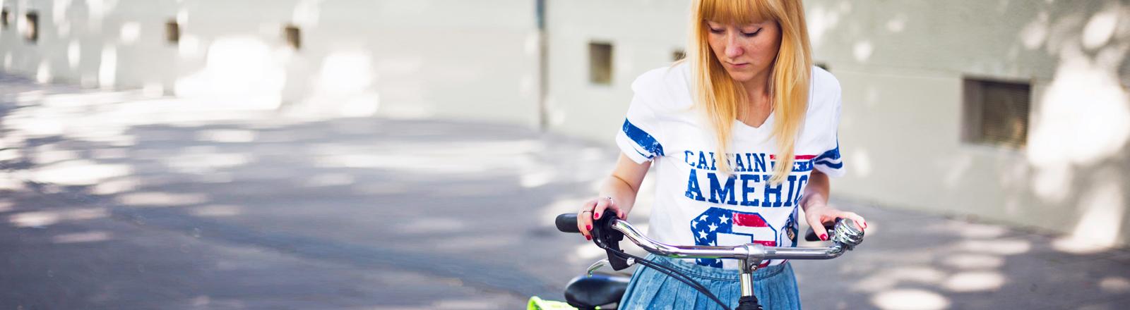 Eine Frau mit Fahrrad trägt ein Shirt: Captain Amerika.