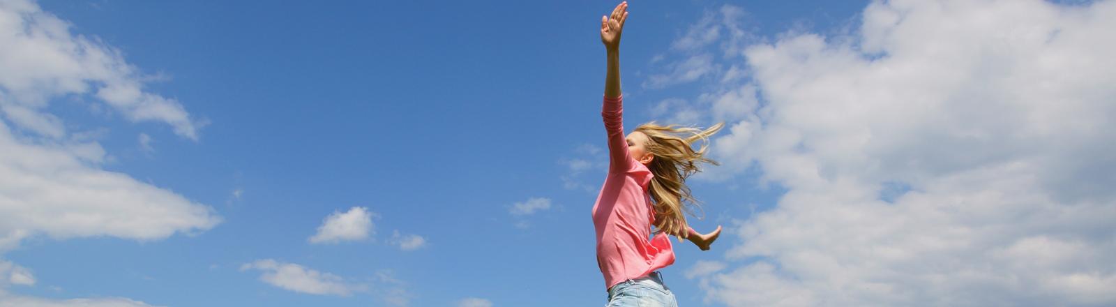 Eine Frau springt über eine Wiese.