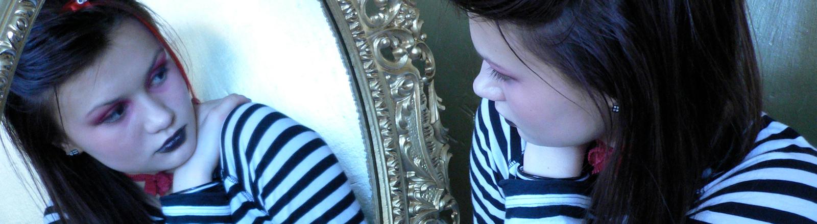 Frau blickt in den Spiegel