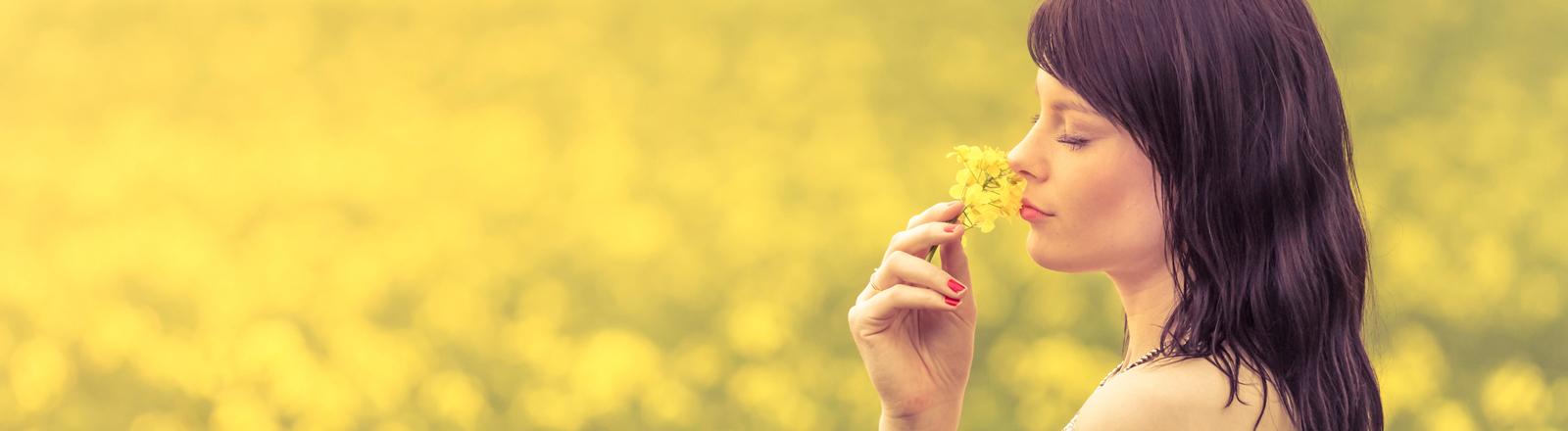 Eine Frau steht völlig sorglos in einem Rapsfeld und riecht an einer Blume.