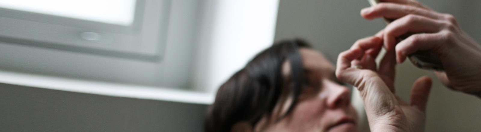 Eine Frau tippt im Liegen in ihr Smartphone. Die Stimmung ist düster.