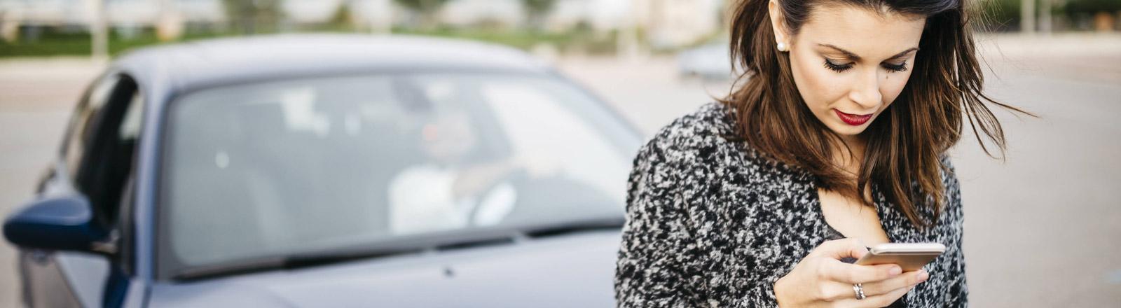 Eine Frau mit Smartphone in der Hand vor einem Auto