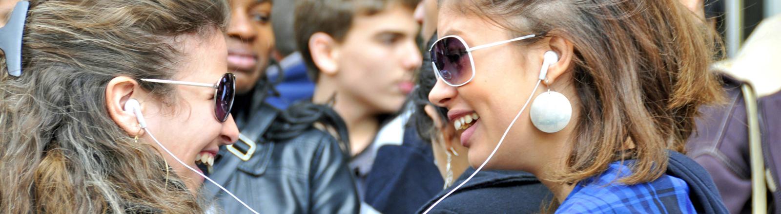 Zwei Mädchen unterhalten sich und sind mit In-Ear-Kopfhörern verbunden.