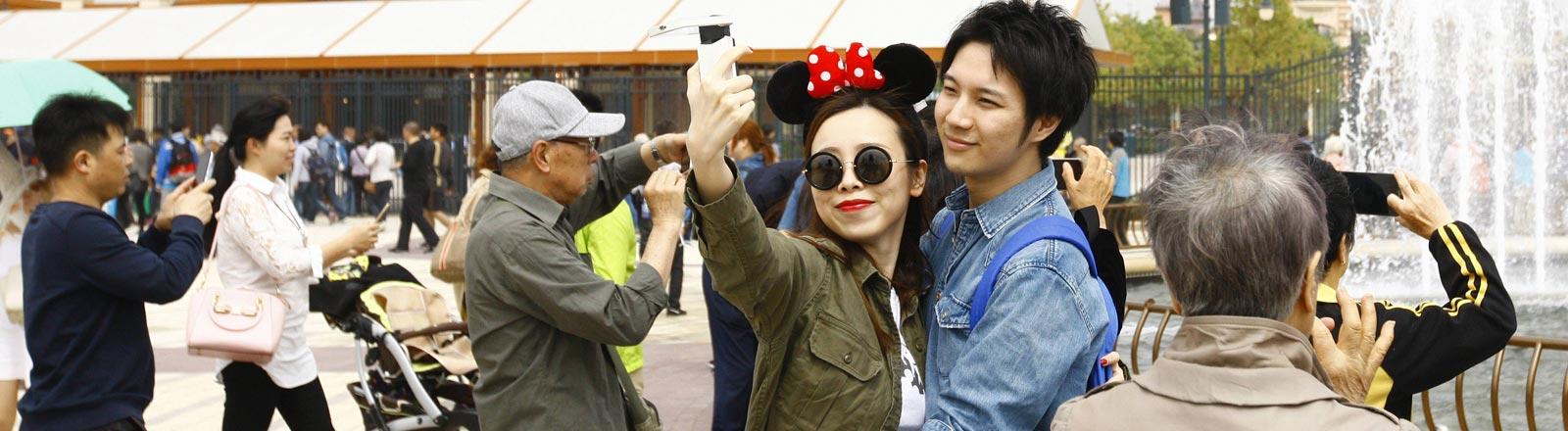 Zwei Besucher des Disneyland Parks in Shanghai machen ein Selfie.