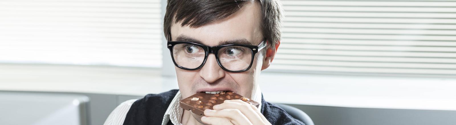 Ein mann im Büro, man könnte auch sagen Nerd, beißt in ein Stück Nussschokolade.