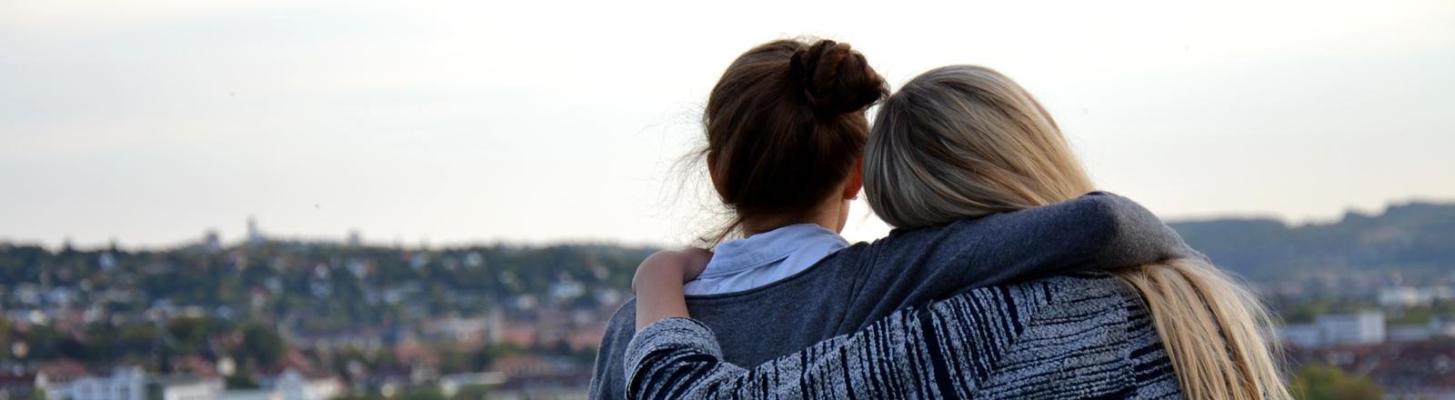 Zwei Jugendliche liégen sich in den Armen und schauen sehnsuchtsvoll auf eine Stadt.