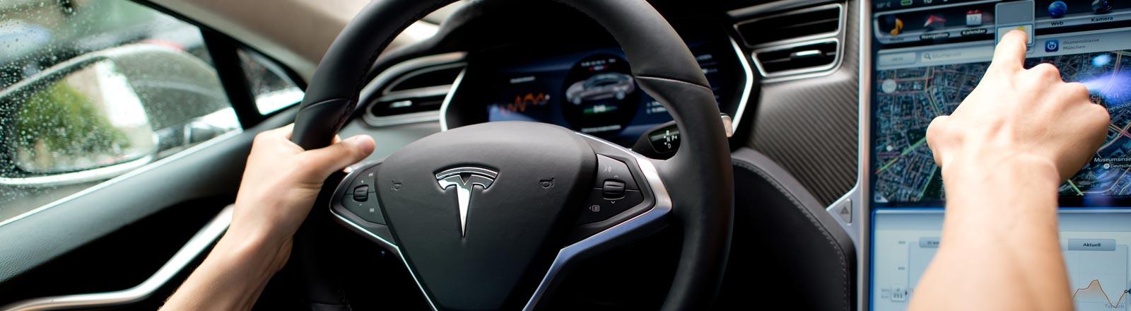 Ein Tesla-Fahrer deutet auf ein Display neben dem Lenkrad.