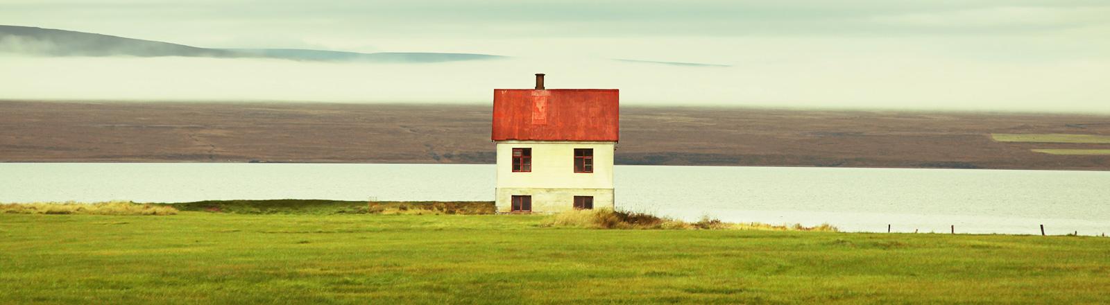 Ein Haus scheint im Wasser zu stehen. Davor eine Wiese, dahinter endlose Weite.