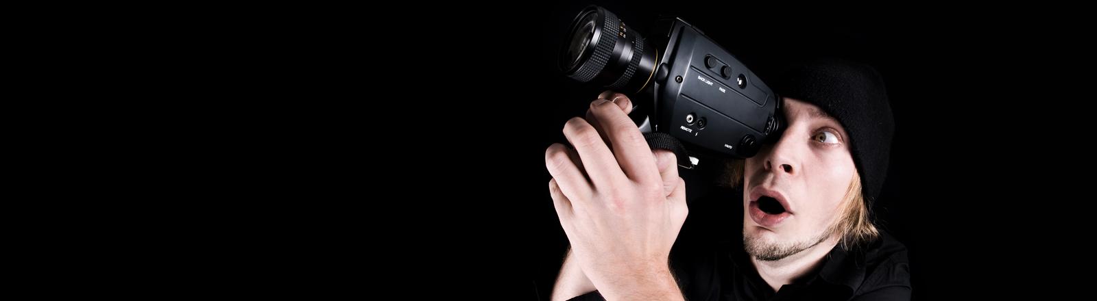 Ein Mann schaut staunend durch seine Videokamera.