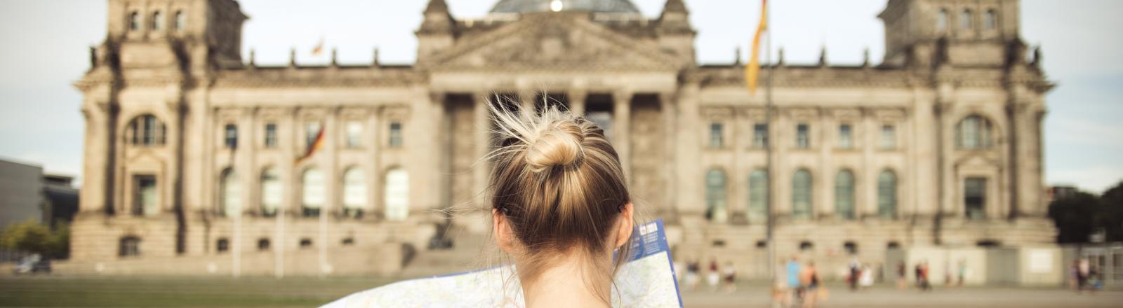 Frau steht vorm Reichstagsgebäudes in Berlin