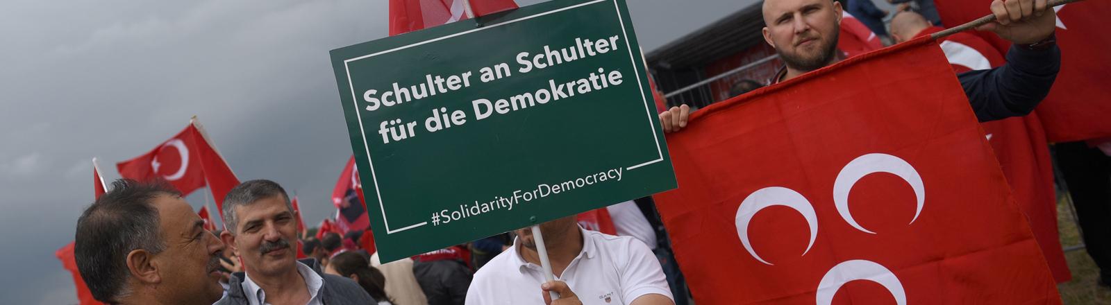 Anhänger des türkischen Staatspräsidenten Erdogan warten am 31.07.2016 in Köln (Nordrhein-Westfalen) auf den Beginn der Kundgebung. Ein Demonstrant hält dabei die Fahne der Grauen Wölfe (MHP).