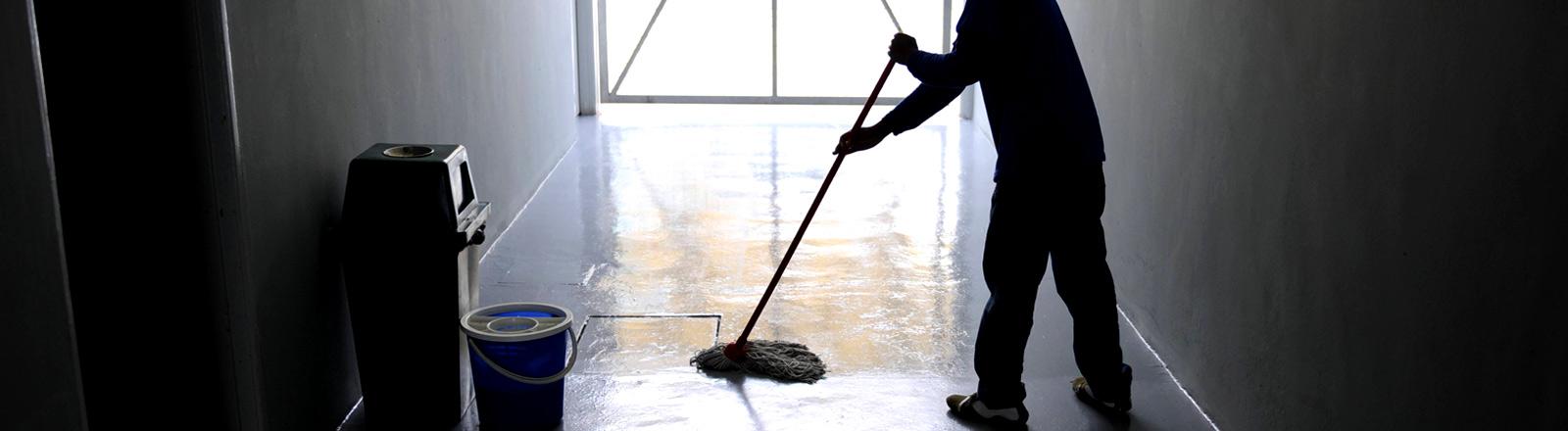 Ein Mann putzt im Schatten einen Hausflur