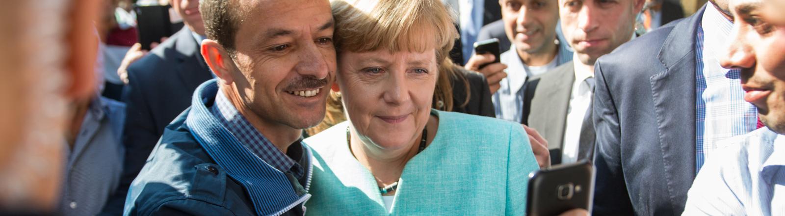 Bundeskanzlerin Angela Merkel (CDU) lässt sich am 10.09.2015 nach dem Besuch einer Erstaufnahmeeinrichtung für Asylbewerber der Arbeiterwohlfahrt (AWO) und der Außenstelle des Bundesamtes für Migration und Flüchtlinge in Berlin-Spandau für ein Selfie zusammen mit einem Flüchtling fotografieren.