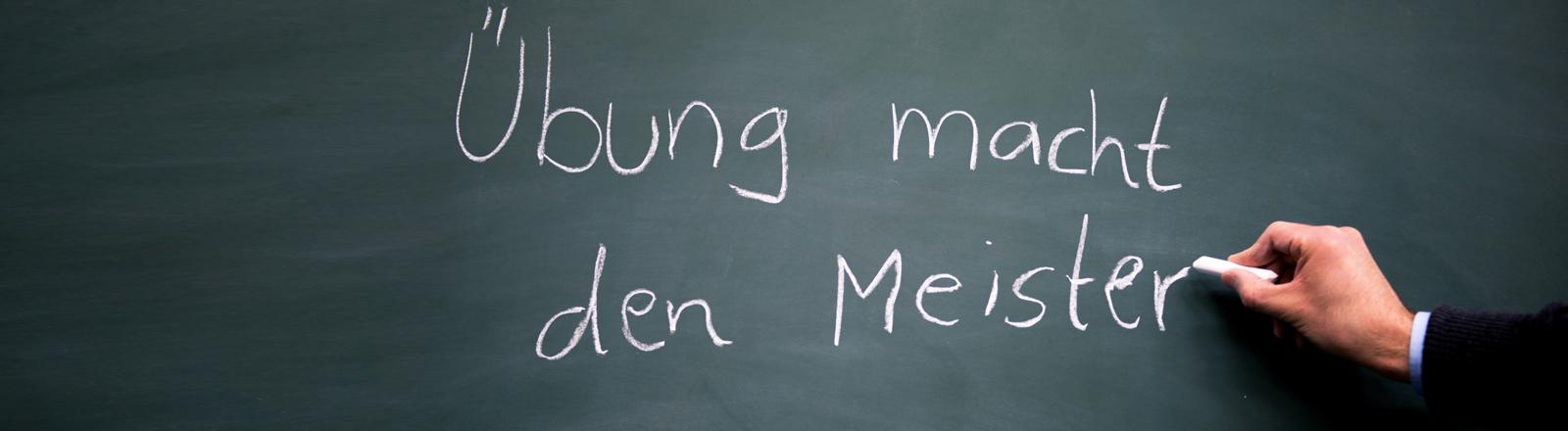 """An einer Tafel steht das Sprichtwort """"Übung macht den Meister""""."""