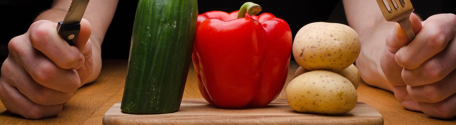 Ein Mann sitzt mit Messer und Gabel hinter einem Brett mit Gemüse.