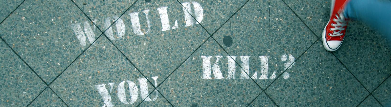 """Auf dem Asphalt stehen die mit Graffiti gesprühte Frage """"Would you kill?"""""""