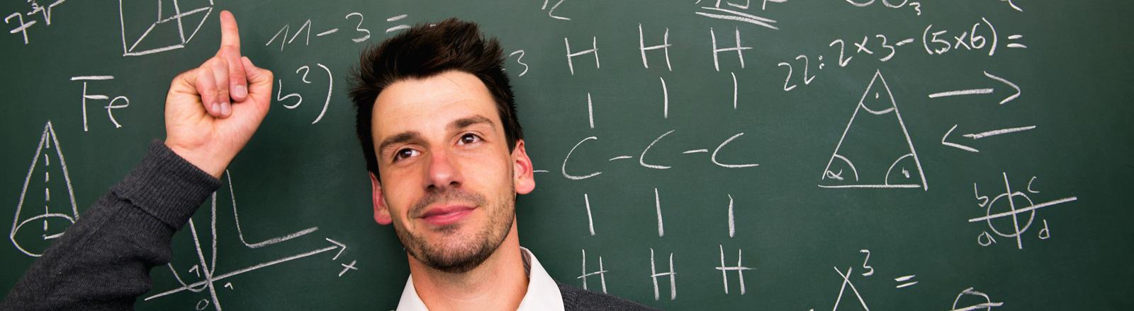 Ein Mann steht vor einer Tafel und streckt den linken Zeigefinger in die Höher. Auf der Tafel stehen mathematische Formeln.