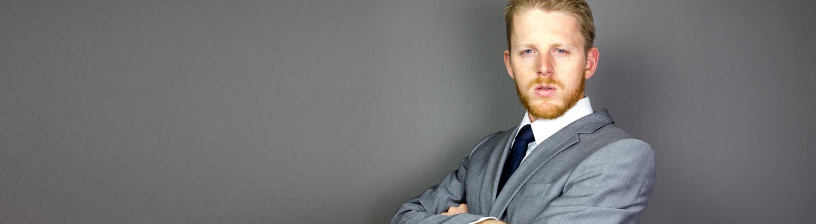 Ein junger Mann mit roten Haaren im grauen Anzug schaut arrogant und machtbesessen in die Kamera