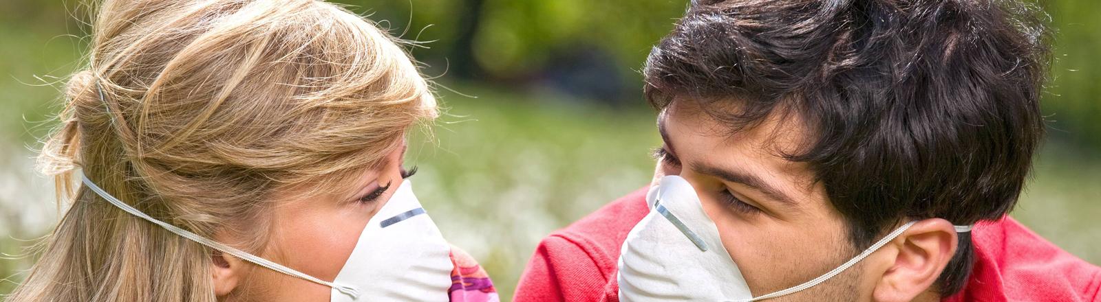 Ein junges Paar liegt in einer Blumenwiese und trägt Mundschutz. Aus Angst vor Allergien.
