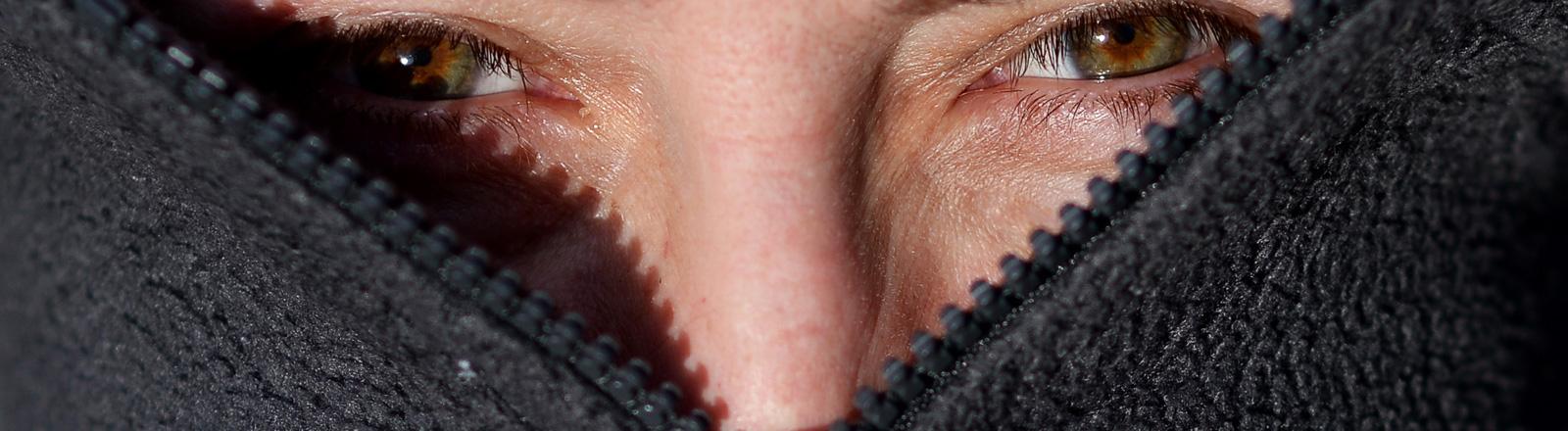 Frau versteckt ihr Gesicht in einer Fleece-Jacke.