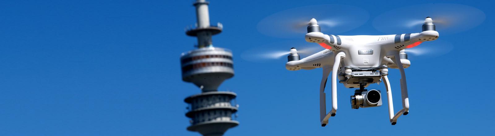 Eine Drohne fliegt in der Luft, im Hintergrund ist ein Fernsehturm zu sehen
