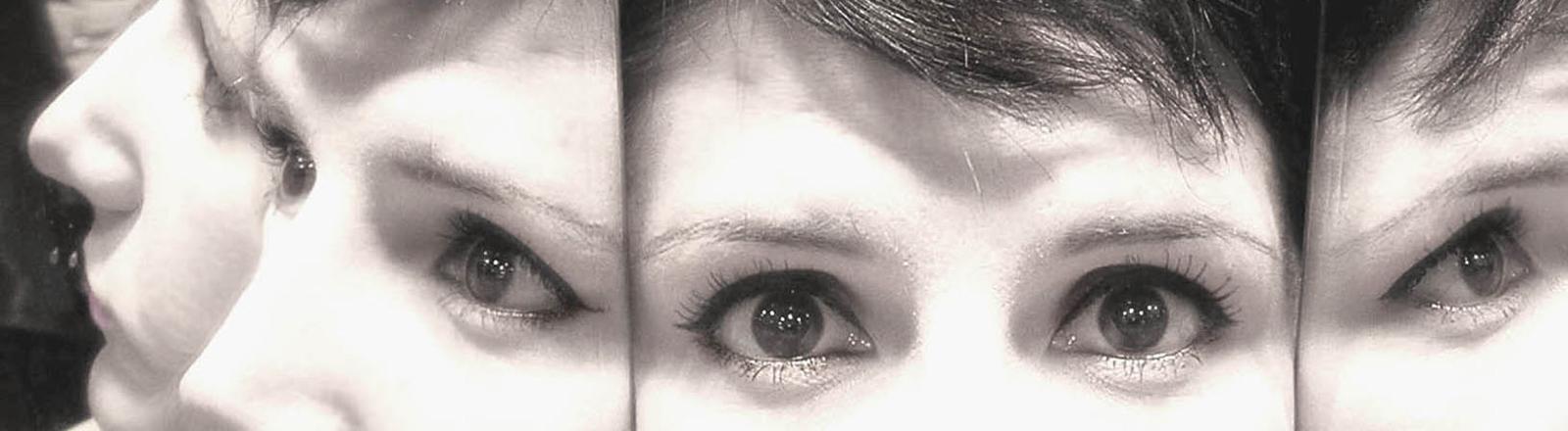 Eine Frau in einem Spiegel. Symbolbild für viele Persönlichkeiten.