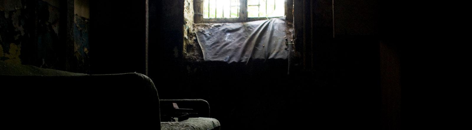 Altes dunkles Zimmer, in das durch ein Fenster Licht fällt