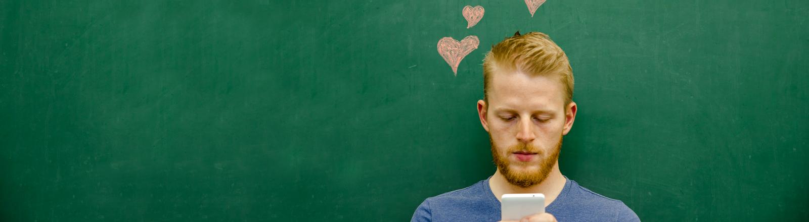 Ein Mann mit einem Smartphone und Herzen auf einer Tafel hinter ihm.