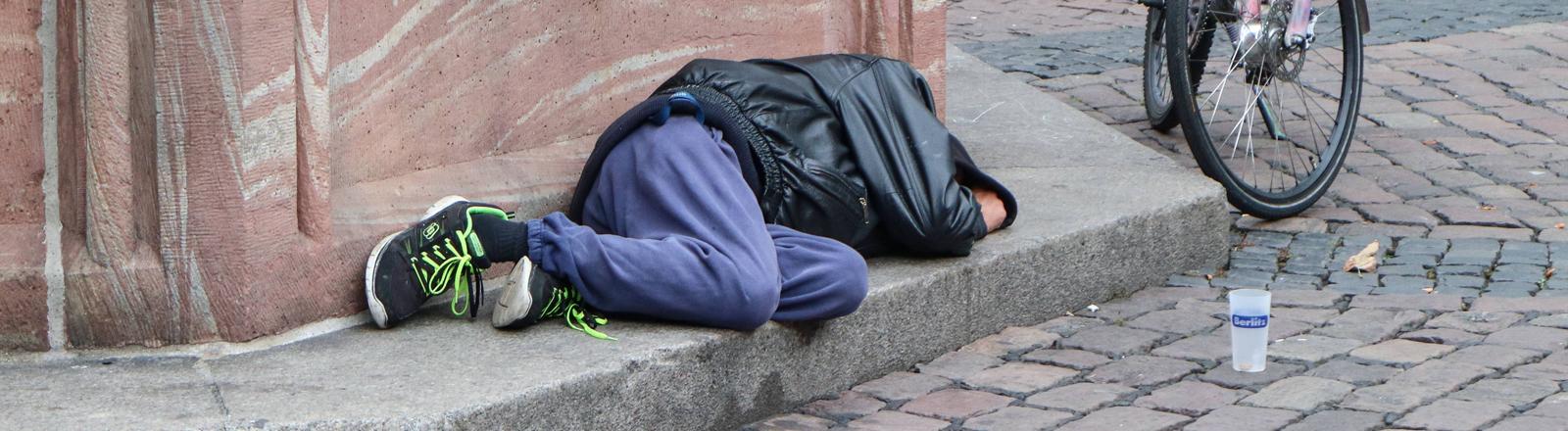 Ein Mann, der auf der Straße schläft.
