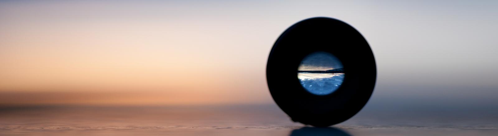 Ein Teleskop liegt auf dem Boden, den Horizont sieht man durch das Guckloch scharf.