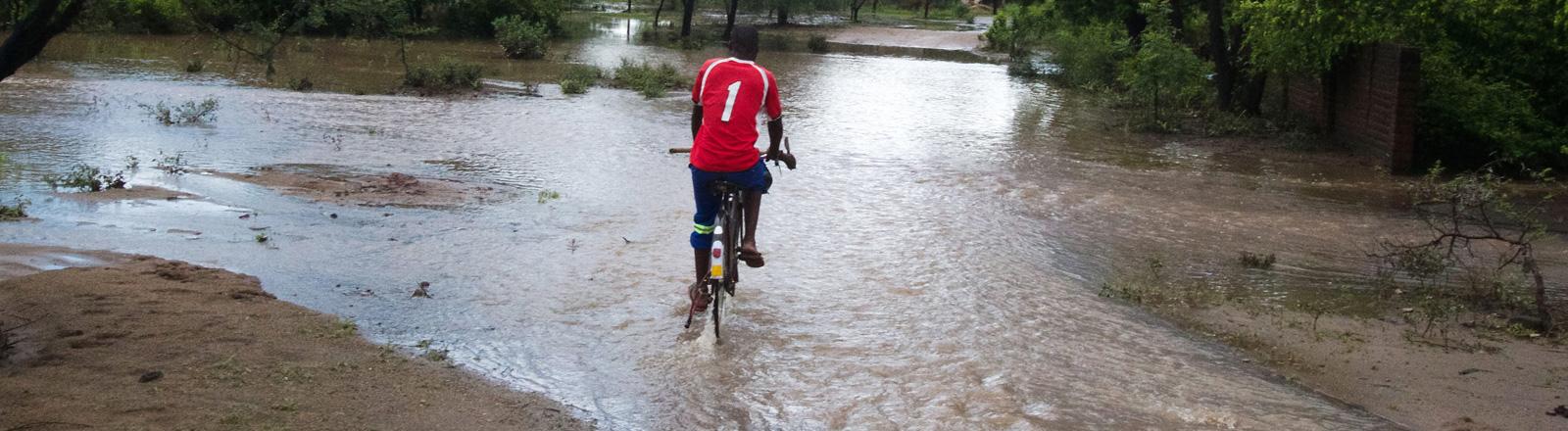 Ein Mann fährt mit dem Fahrrad durch überflutetes Gebiet in Malawi.