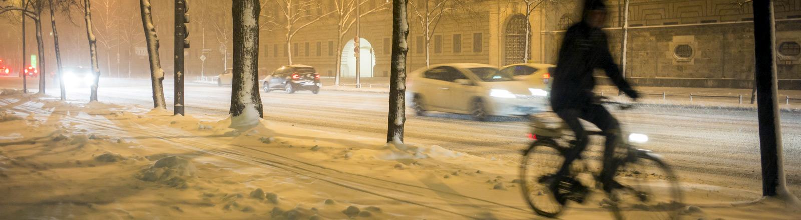 Ein Mann fährt Rad auf einem verschneiten Radweg.
