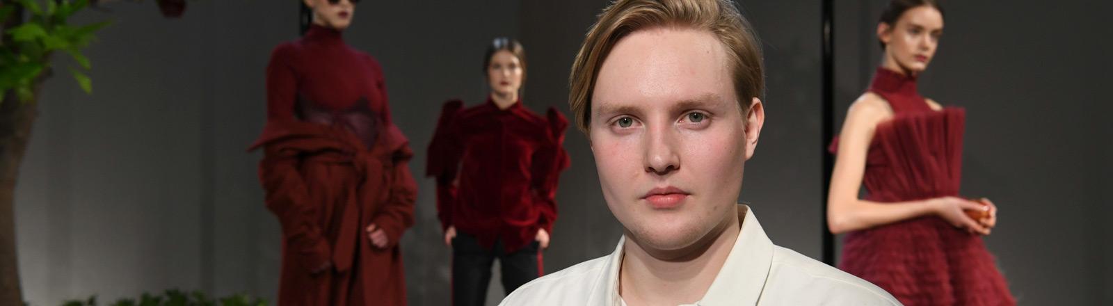Danny Reinke -  im Hintergrund sieht man Models, die von ihm entworfene Kleider tragen.