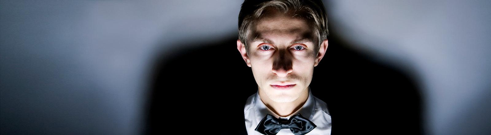 Ein bedrohlich wirkender junger Mann mit einem weißen Hemd und einer Fliege.