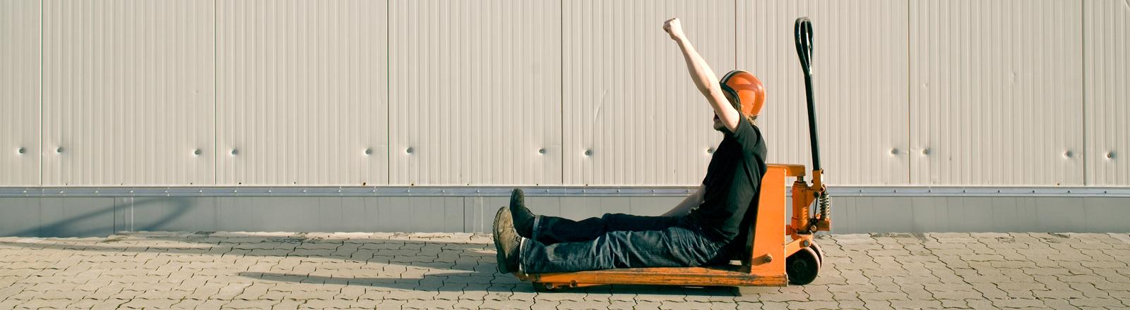 Ein Mann sitzt auf einem Gabelstapler. Ein Dude.