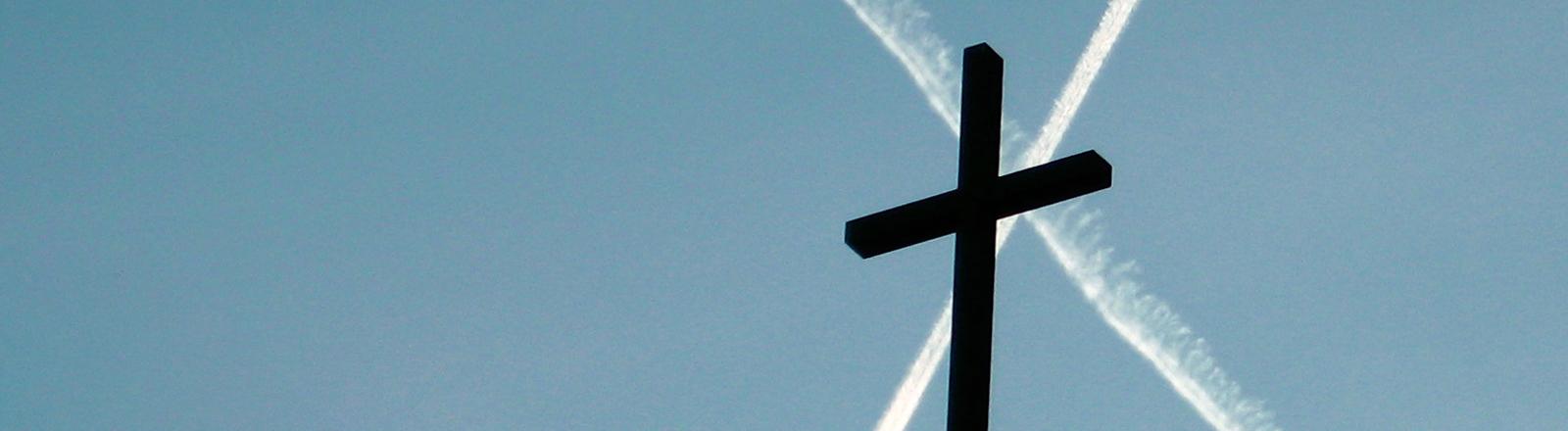 Eine Kirche ein Kreuz vor Chemtrails. Symbolbild für konservative Verschwörungstheoretischer.