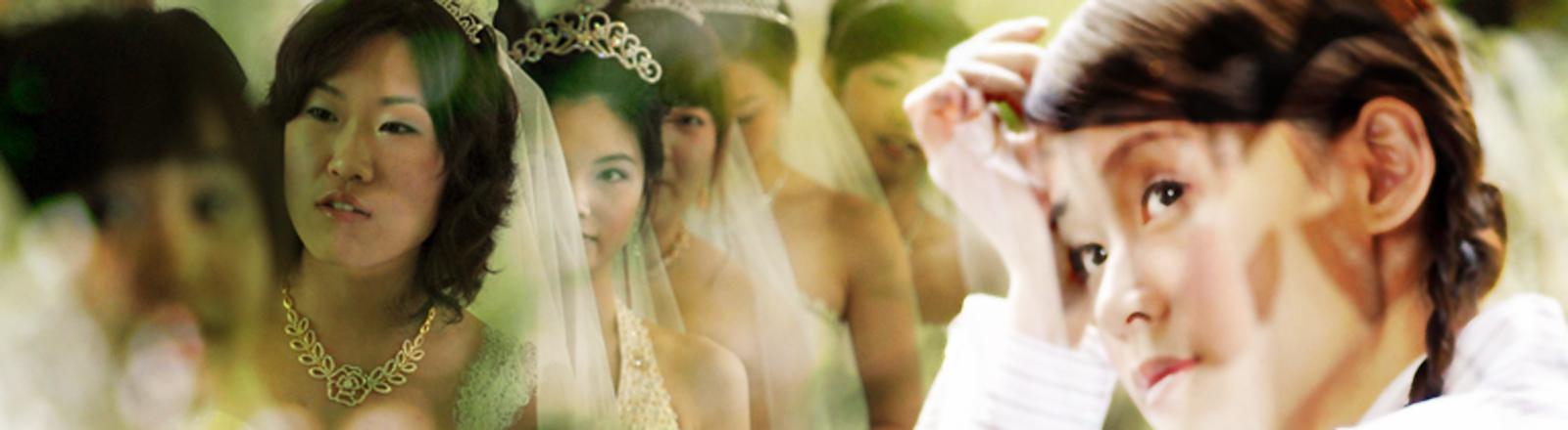 Eine Chinesin blickt sehnsuchtsvoll auf Frauen im Hochzeitskleid.