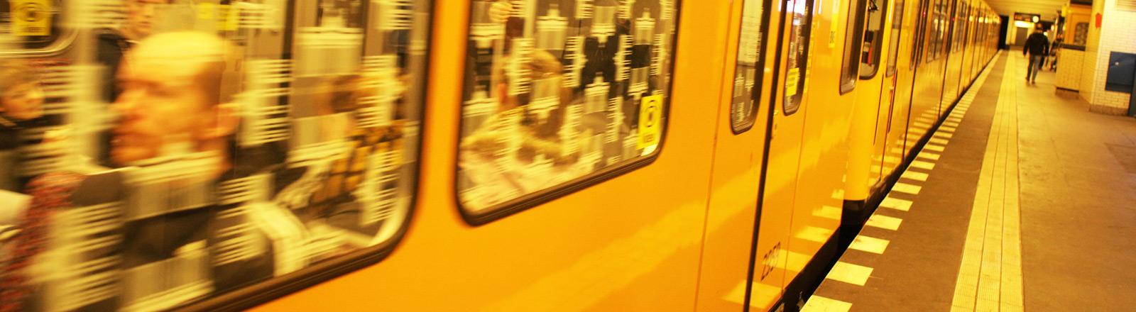 Eine Berliner U-Bahn hält an einer Haltestelle.