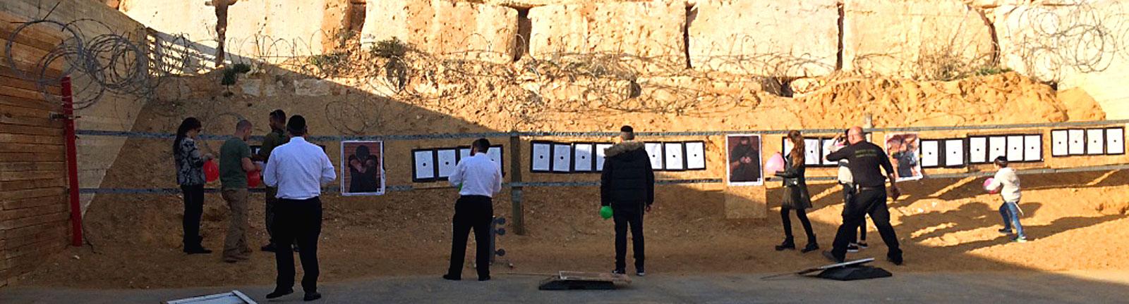 Touristen in Israel stehen vor einer Mauer an der Zielscheiben hängen